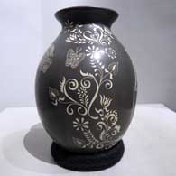 Sgraffito geometric design on a black and white jar