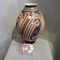 Lightly carved, sgraffito and painted geometric design on a large polychrome vase