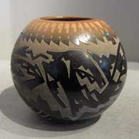 Sgraffito avanyu, feather and geometric design on a black jar with sienna rim and spots