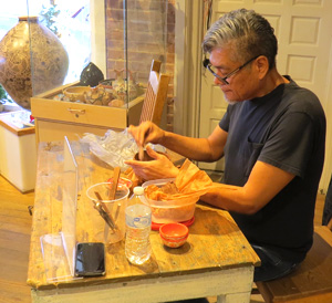 Hubert Candelario smoothing the inside of a piece he is just forming