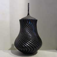 Lidded, polished black jar carved with swirl design , click or tap to see a larger version