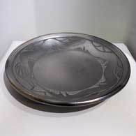 Black plate with sgraffito avanyu design Last month , click or tap to see a larger version