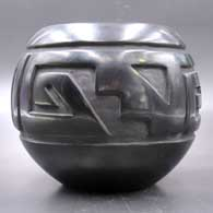 Black jar carved with a four-panel geometric design, click or tap to see a larger version