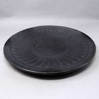 Black on black plate with ring of feathers design, click or tap to see a larger version