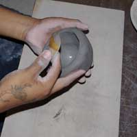 Using a piece of gourd to work the clay outwards