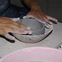 Pushing the clay into a bowl form