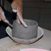 Smoothing the first clay cloil to the bowl